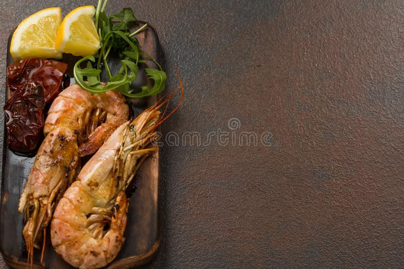Fried tiger shrimps with lemon, sun-dried tomatoes and greens or rukkola on a dark wooden cutting board. royalty free stock photography