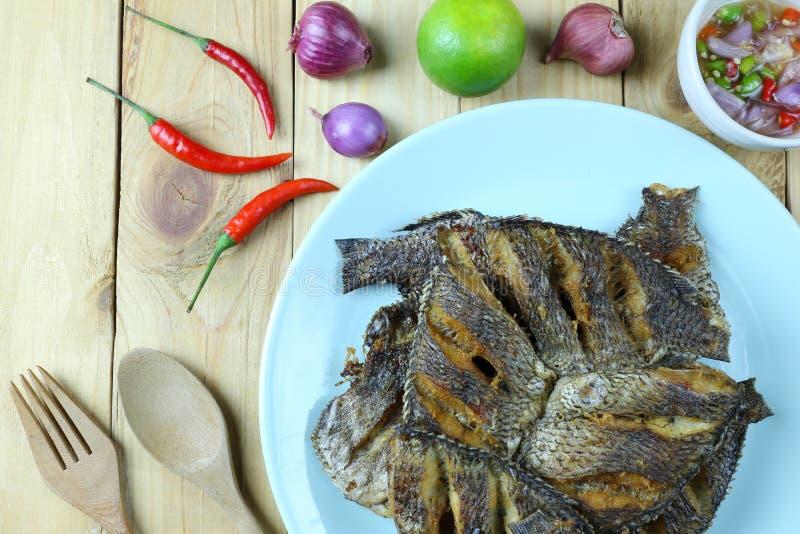 Fried tilapia in dish. On wooden floor of Thai sea foods stock image