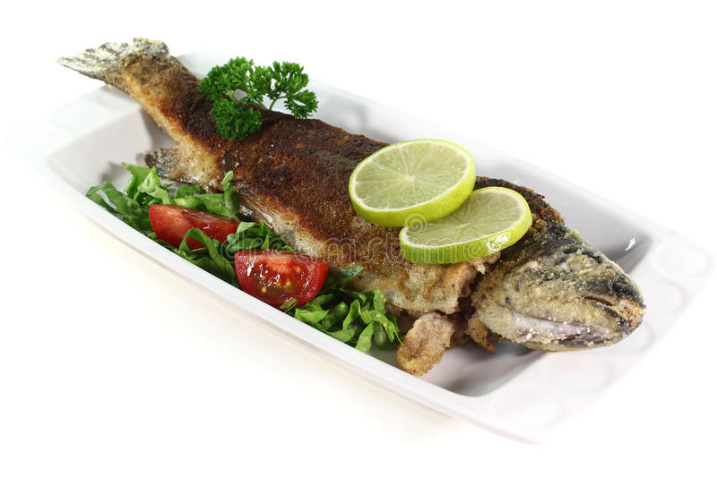 Fried trout. Fresh trout Miller with lettuce, tomatoes and lime royalty free stock images