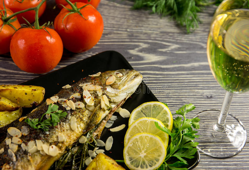 Fried trout with almonds stock photos