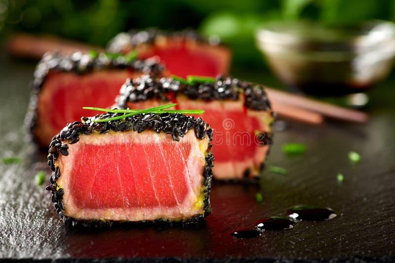 Fried tuna steak in black sesame with chopsticks stock image
