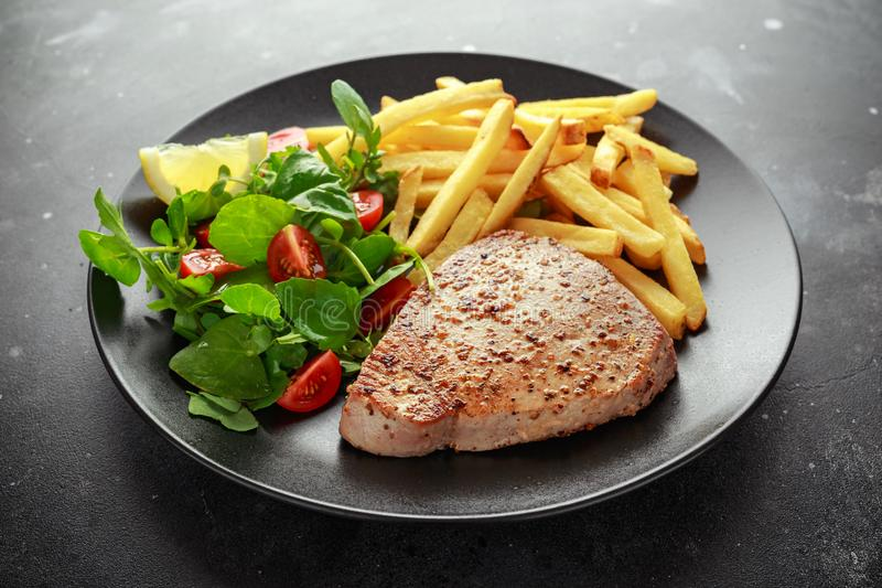 Fried Tuna Steaks on Black Plate with Fresh Green, Tomato Salad, lemon and french fries. healthy sea food stock photography