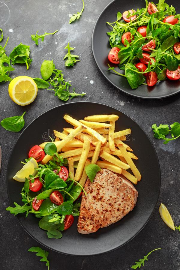 Fried Tuna Steaks on Black Plate with Fresh Green, Tomato Salad, lemon and french fries. healthy sea food.  stock images