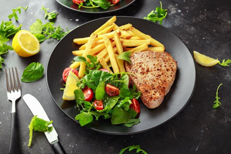 Fried Tuna Steaks na placa preta com verde fresco, salada do tomate, limão e batatas fritas Alimento de mar saudável imagem de stock