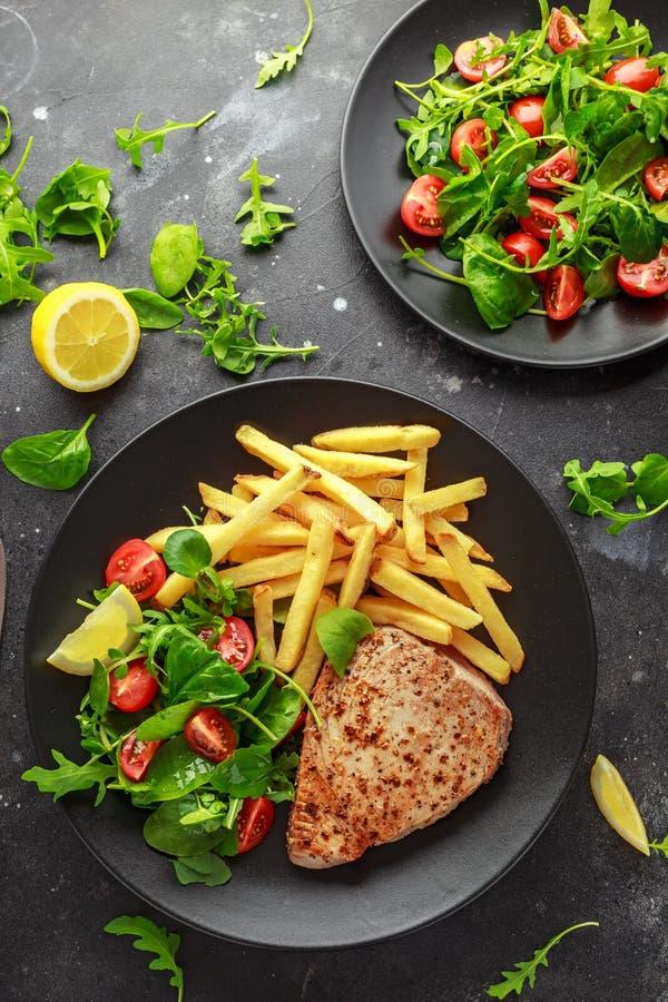 Fried Tuna Steaks na placa preta com verde fresco, salada do tomate, limão e batatas fritas Alimento de mar saudável imagens de stock