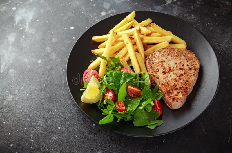 Fried Tuna Steaks op Zwarte Plaat met Verse Groene, Tomatensalade, citroen en frieten Gezond overzees voedsel royalty-vrije stock afbeeldingen