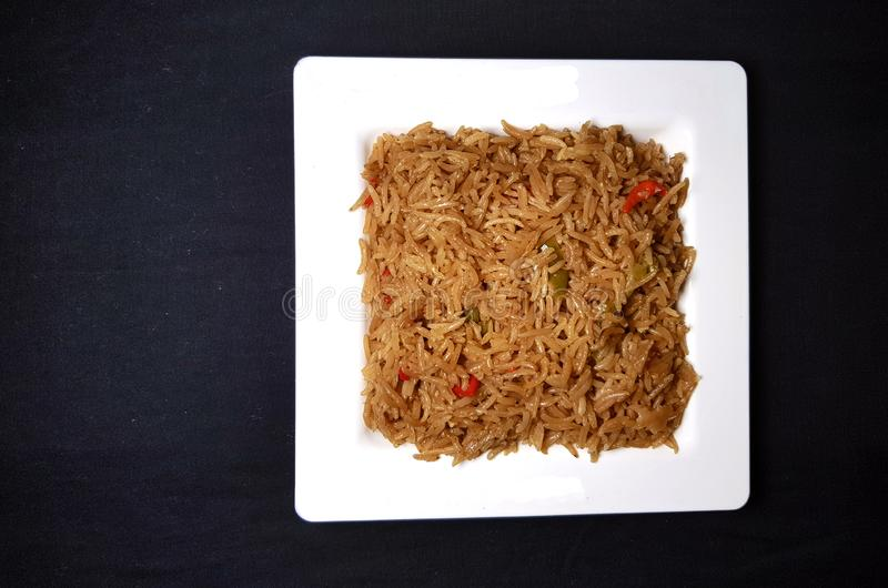 Fried vegetable rice. In white plate on black background royalty free stock image