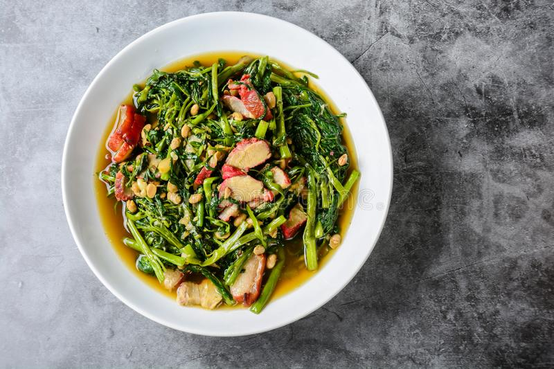 Fried water spinach with barbecued red pork stock photography