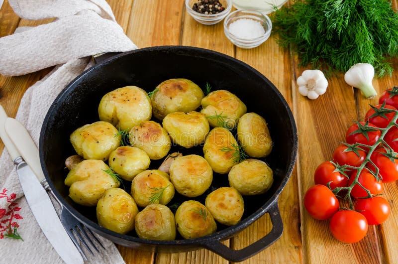 Fried Young Potatoes in een gietijzerpan met knoflook en dille stock foto's
