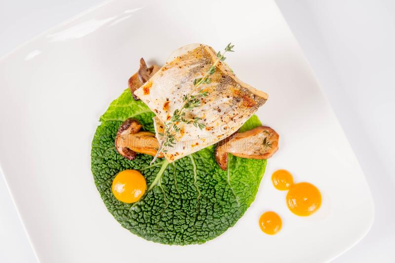Fried zander. Millet with green vegetables, fried boletus with thyme on a green leaf with some egg yolks on a white background stock photos
