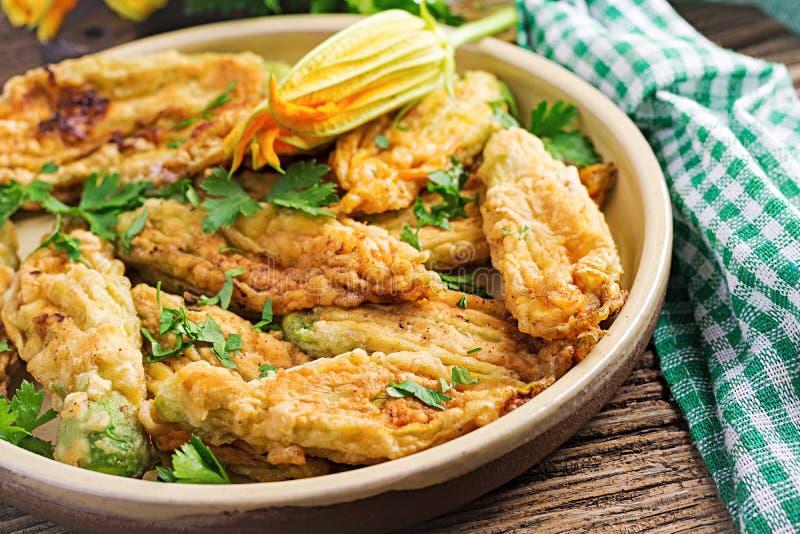 Fried zucchini flowers stuffed with ricotta and green herbs. Vegan food. Italian cuisine stock image