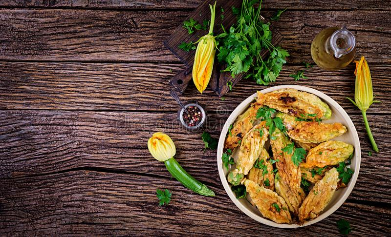 Fried zucchini flowers stuffed with ricotta and green herbs. Vegan food. Italian cuisine. Top view royalty free stock image
