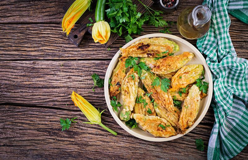 Fried zucchini flowers stuffed with ricotta and green herbs. Vegan food. Italian cuisine. Top view stock image