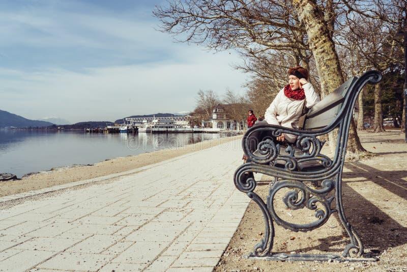 Friedelstrand, riva del sud Wörthersee, Klagenfurt, Carinzia, Austria - 20 febbraio 2019: Una donna che si siede su un banco di  fotografia stock