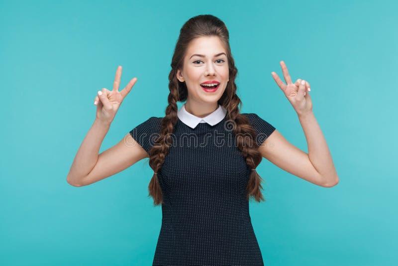 Frieden, optimistischer Blick! Junge Frau des Glückes, die v-Zeichen zeigt stockfoto