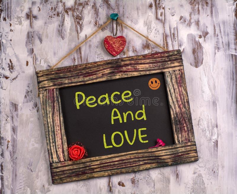 Frieden und Liebe geschrieben auf Weinlesezeichenbrett lizenzfreie stockbilder