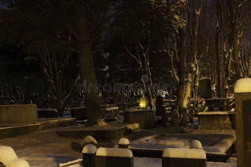 Friedhof auf einem kalten schneebedeckten Winterabend stockbild