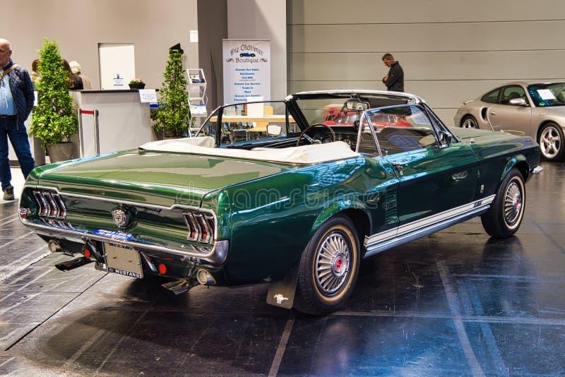 FRIEDRICHSHAFEN - MAJ 2019: mörk smaragd - den gröna FORD MUSTANGET T5 GT SAMLAR cabrioen 1966 på Motorworld klassiker Bodensee p royaltyfria bilder