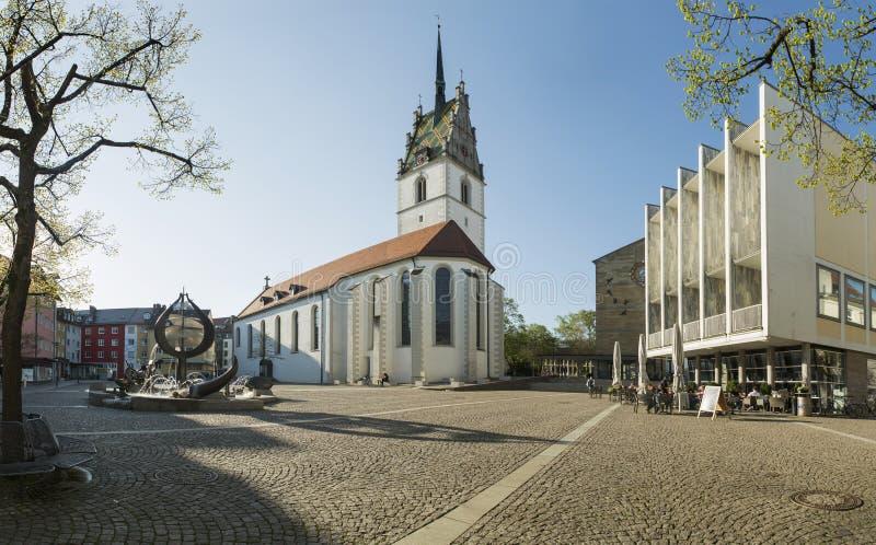 FRIEDRICHSHAFEN TYSKLAND - APRIL 20, 2016: St Nikolaus Church och stadshus i Friedrichshafen arkivfoton