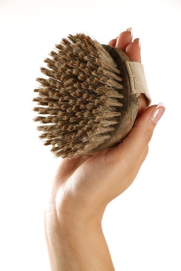 Friegue el cepillo en una mano femenina hermosa fotos de archivo