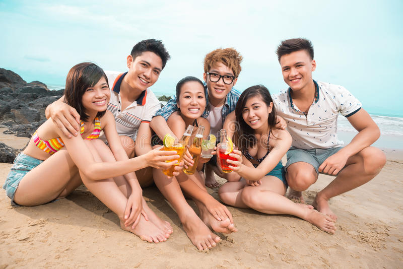 Friend�s toasting. Portrait of young people at beach toasting and looking at camera stock photography