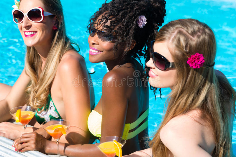 Friend drinking cocktails in swimming pool bar. Three women friends drinking cocktails in swimming pool bar, African and Caucasian girls royalty free stock photo