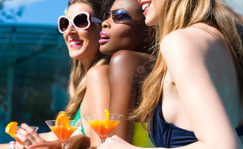 Friend drinking cocktails in swimming pool bar. Three women friends drinking cocktails in swimming pool bar, African and Caucasian girls royalty free stock photos
