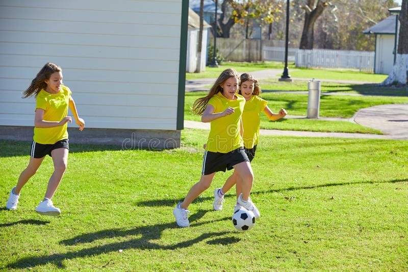 Friend girls teens playing football soccer in a park stock photo