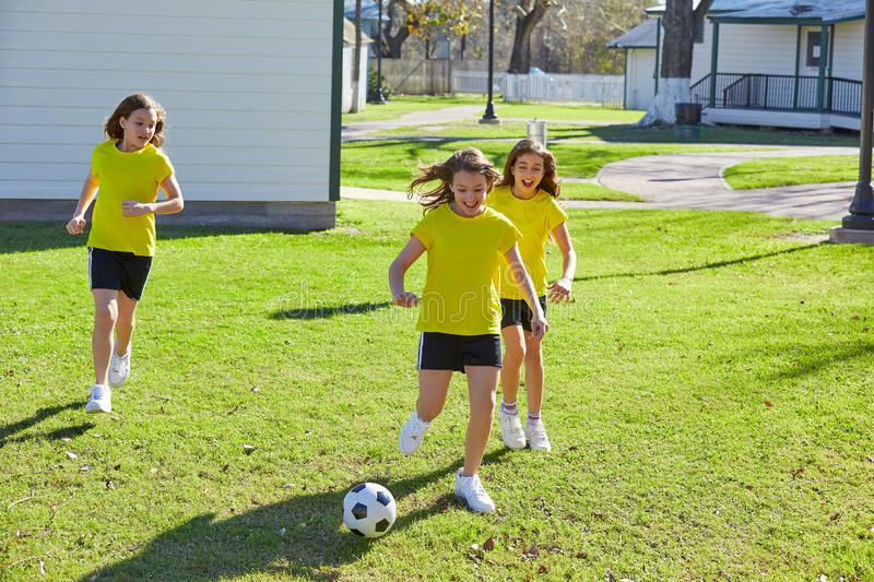 Friend girls teens playing football soccer in a park royalty free stock photography