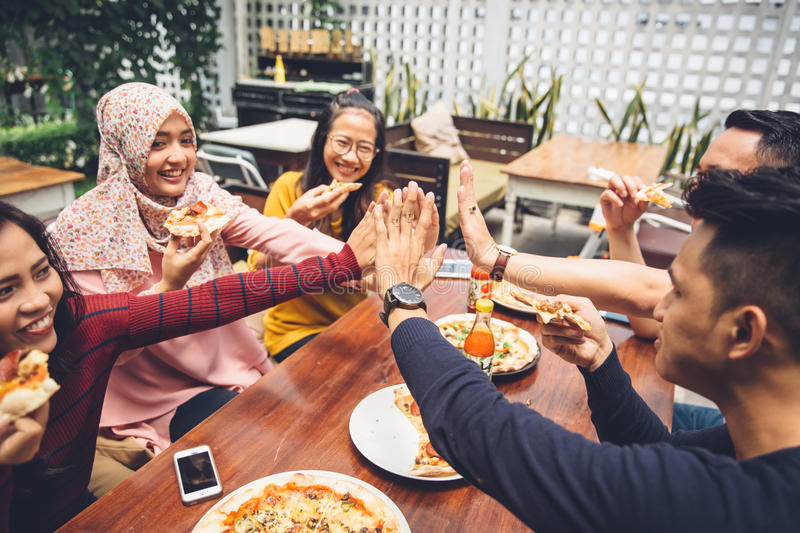 Friend giving high five at cafe. Portrait of asian friend giving high five at cafe while having a lunch royalty free stock photos