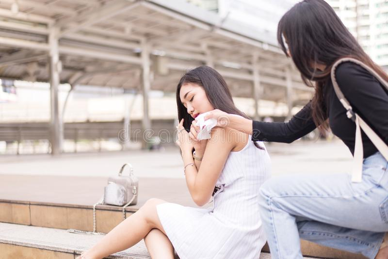 Friend giving tissue to depressed asian woman,Unhappy female support her girl friend outdoor,Mental health care concept stock images