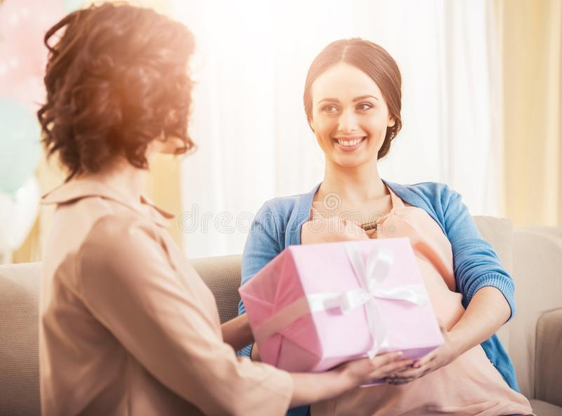 Friend Giving to Pregnant Woman Gift in Pink Box. royalty free stock images