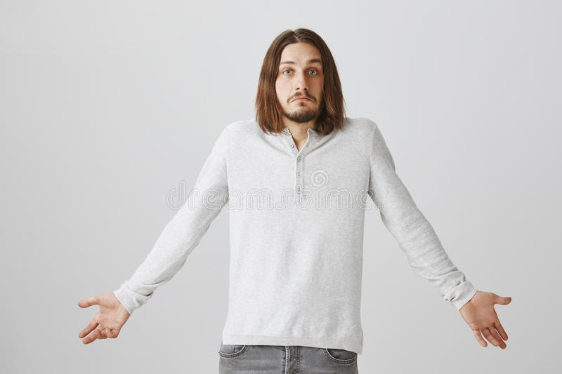 Friend have no clue and no answer on question. Portrait of attractive young bearded guy with long hair shrugging with. Spread hands, pouting, being confused and stock image