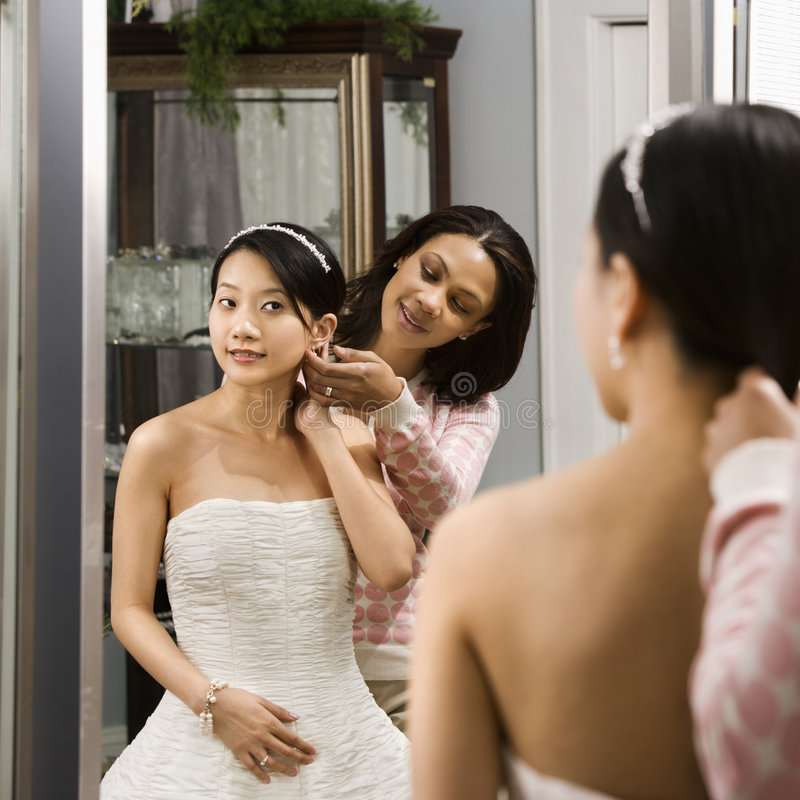 Friend helping bride. African-American woman helping Asian bride with hair stock photo