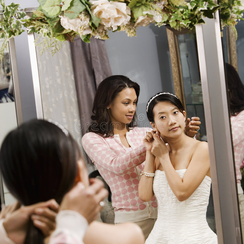 Friend helping bride. African-American woman helping Asian bride with hair royalty free stock photo