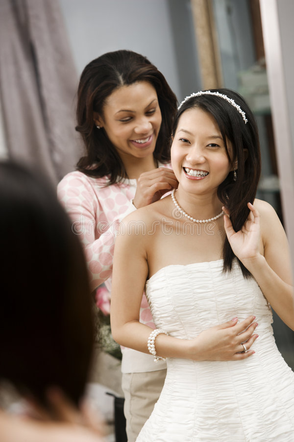 Friend helping bride. African-American friend helping place necklace on Asian bride royalty free stock photos
