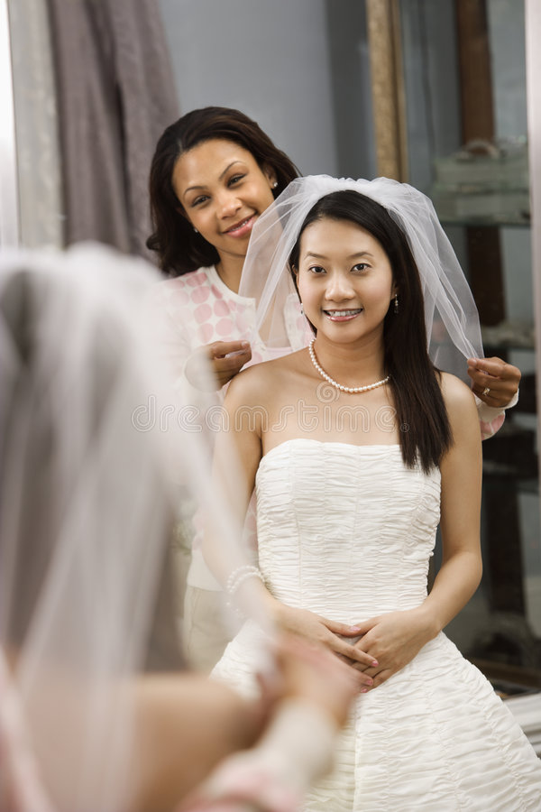 Friend helping bride. African-American friend holding Asian bride's veil stock images
