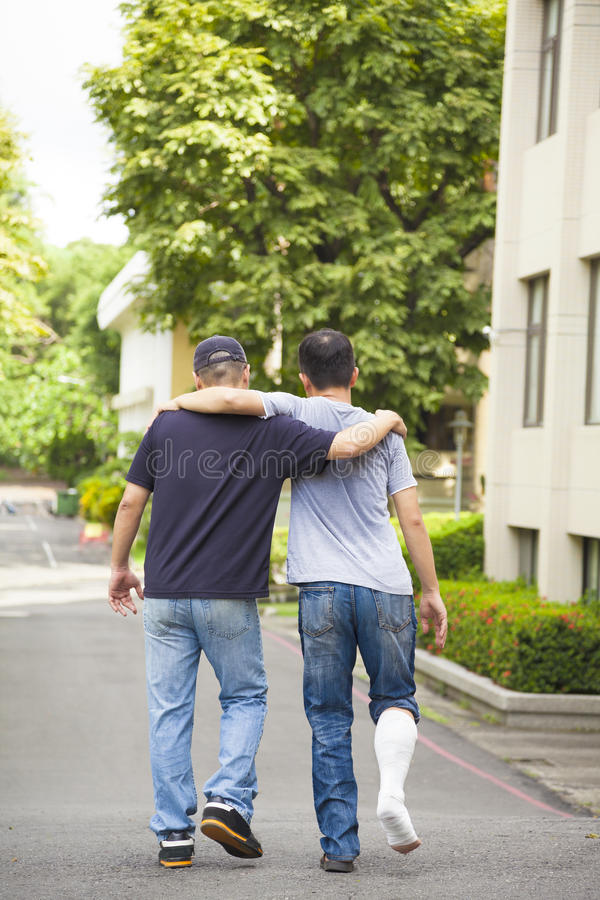 Friend helping brothers or patient to walk without crutches. In the park royalty free stock photography