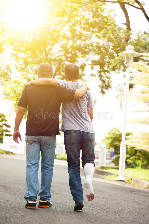 Friend helping brothers or patient to walk on the road. In outdoors royalty free stock photos