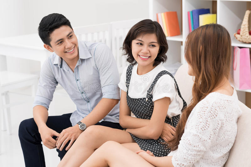 Friend's chatting. Friends sitting and chatting together at home royalty free stock images