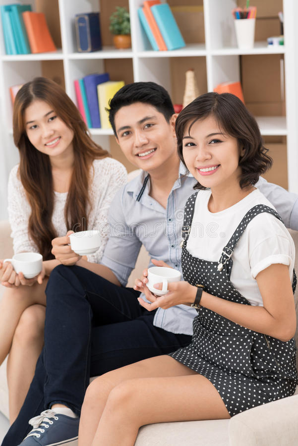 Friend's portrait. Vertical portrait of Asian friends drinking tea together at home royalty free stock images