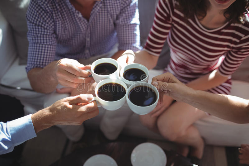 Friend toasting coffee cups together stock photography