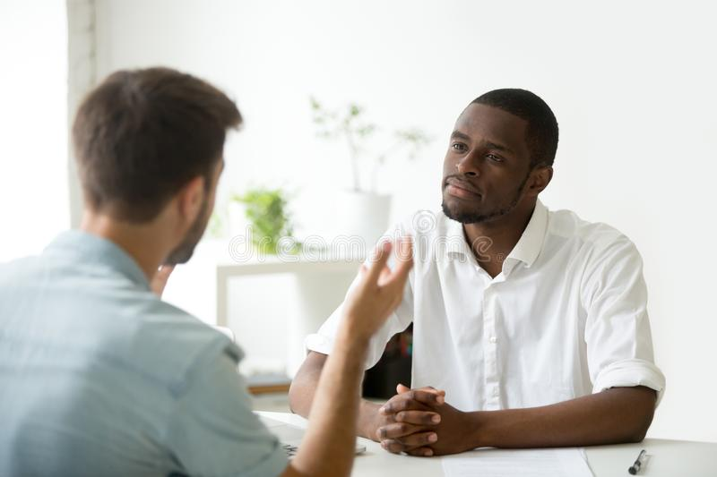 Friendly African American employer listening to work candidate d royalty free stock photo