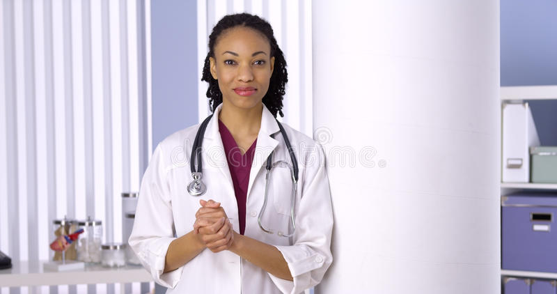 Friendly African woman doctor standing in office royalty free stock photos