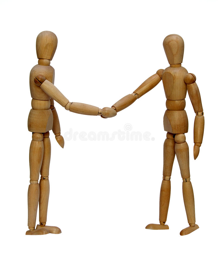 The friendly agreement. Symbolical acceptance of the agreement on an example of wooden dolls royalty free stock photography