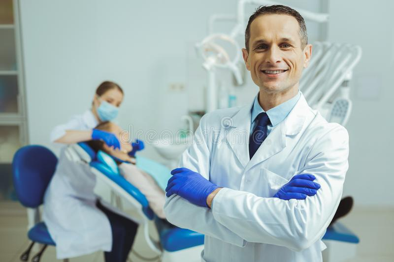 Handsome dentist smiling on camera. Friendly atmosphere. Silhouette of stomatologist that sitting near patient and examining bad teeth stock image