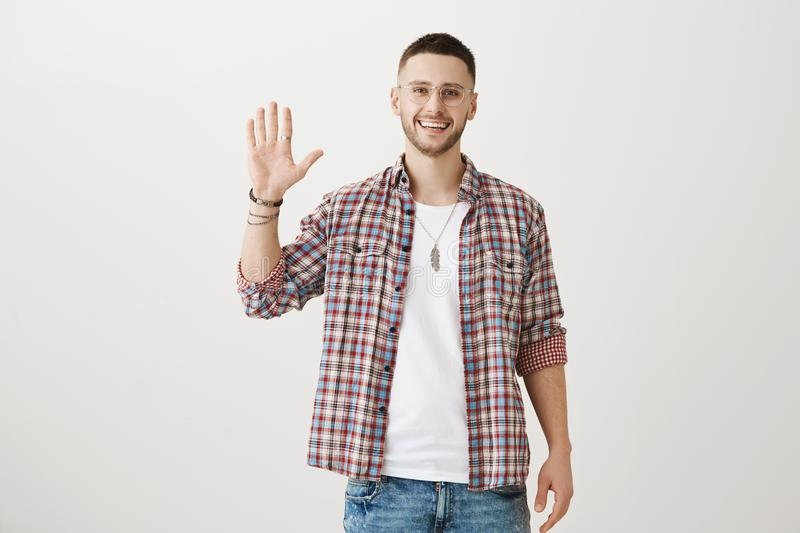 Friendly attractive male sportsman in trendy clothes and glasses raising palm to greet friend or give high five, smiling royalty free stock photos
