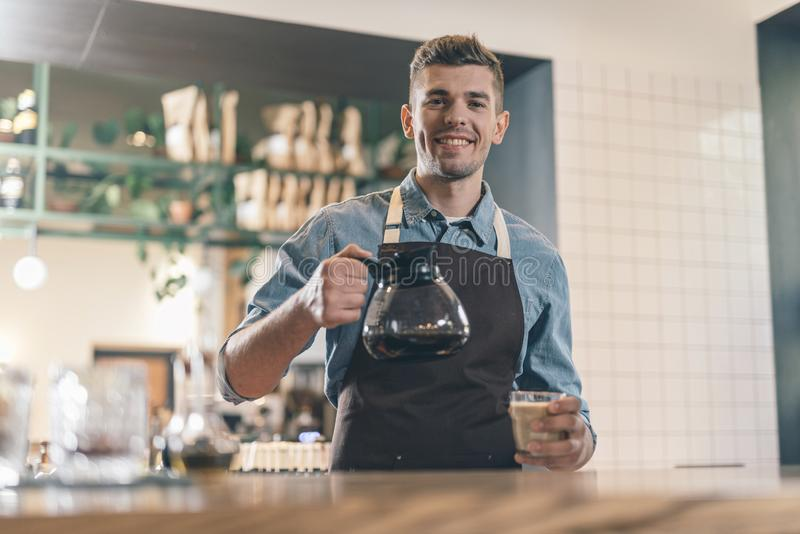 Friendly barista smiling at the camera while holding coffee stock photos