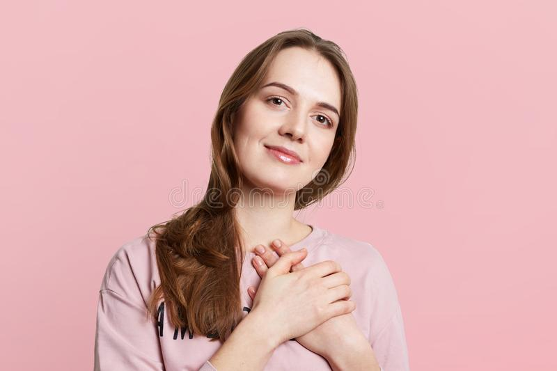 Friendly brunette female keeps hands on heart, expresses good feelings, has pleasant appearance, isolated over pink background. Be stock images