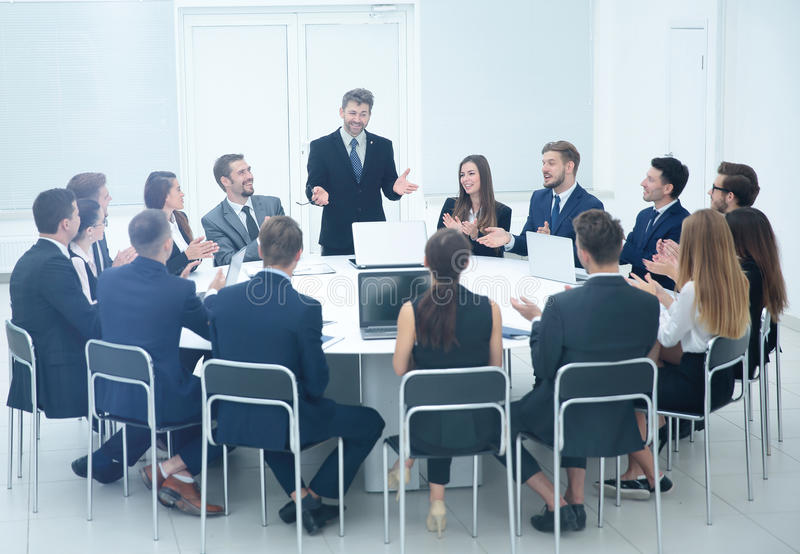 Friendly business team applause greeted his boss before the busi. Large business team sitting at a round table with laptops and applause meets a Director who is stock photos